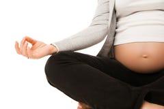 La mujer embarazada se relaja haciendo yoga sobre blanco Imagenes de archivo