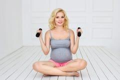 La mujer embarazada sienta y lleva a cabo pesas de gimnasia Fotos de archivo