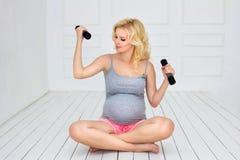 La mujer embarazada sienta y lleva a cabo pesas de gimnasia Imagen de archivo libre de regalías