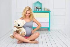 La mujer embarazada sienta y sostiene un oso de peluche Foto de archivo libre de regalías
