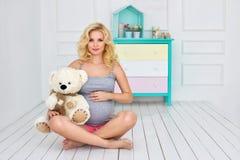 La mujer embarazada sienta y sostiene un oso de peluche Imagen de archivo