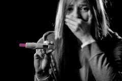 La mujer embarazada triste joven o el adolescente femenino asustó y chocó celebrar resultado positivo de la prueba de embarazo Foto de archivo libre de regalías