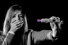 La mujer embarazada triste joven o el adolescente femenino asustó y chocó celebrar resultado positivo de la prueba de embarazo Fotos de archivo libres de regalías