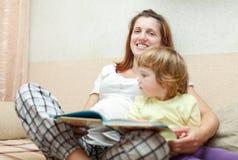 La mujer embarazada y el niño lee el libro Foto de archivo libre de regalías