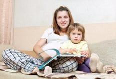 La mujer embarazada y la hija lee el libro Imagen de archivo