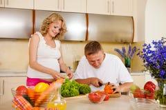 La mujer embarazada y su marido preparan la ensalada vegetal Imagenes de archivo