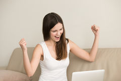 La mujer emocionada dice sí mientras que mira en el ordenador portátil Fotos de archivo
