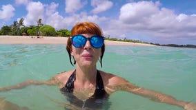 La mujer emocionada feliz con los vidrios azules que se divierten en el océano, le muestra las piernas y el smlinig Cámara lenta, almacen de video