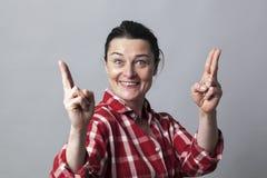 La mujer emocionada que muestra ambas manos le gustan los armas de la diversión para el poder Imagen de archivo