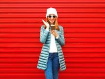 La mujer emocional feliz está riendo con un smartphone en un rojo Foto de archivo libre de regalías