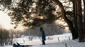 La mujer empuja a un hombre en un banco de la nieve Ambos vestidos en chaquetas azules almacen de metraje de vídeo