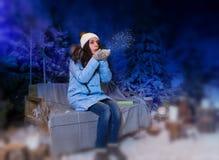 La mujer en abajo chaqueta azul sopla los copos de nieve mientras que se sienta en un interruptor Foto de archivo libre de regalías