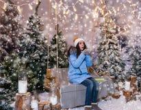 La mujer en abajo chaqueta azul sopla los copos de nieve mientras que se sienta en un interruptor Imagen de archivo libre de regalías