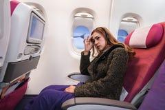 La mujer en aeroplano sufre de mareado en el aire con dolor de cabeza de la tensi?n mide el tiempo en vuelo imagenes de archivo