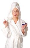 La mujer en albornoz está poniendo la crema Imágenes de archivo libres de regalías