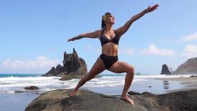 La mujer en armonía con la naturaleza medita la situación en una piedra en la playa cerca del océano almacen de video
