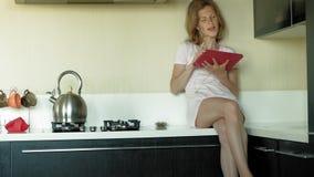 La mujer en auriculares en la cocina utiliza la tableta Ma?ana almacen de video