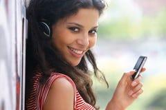 La mujer en auriculares escucha la música tu Imagen de archivo