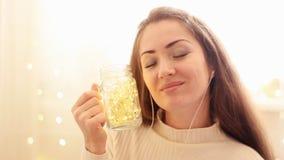 La mujer en auriculares que escucha la música, mirando las luces, se cierra los ojos y se relaja almacen de metraje de vídeo