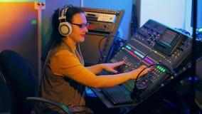 La mujer en auriculares y vidrios mezcla las pistas para el disco en una consola de mezcla almacen de video