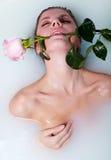 La mujer en baño con se levantó Foto de archivo