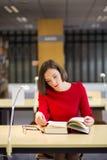 La mujer en biblioteca leyó el libro por razón Fotografía de archivo libre de regalías