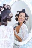 La mujer en bigudíes de pelo pone maquillaje de la mañana Imagenes de archivo