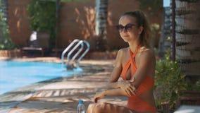 La mujer en bikini utiliza la protección solar para los brazos por la piscina