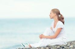 La mujer en blanco relaja la reclinación sobre el mar en la playa Fotografía de archivo