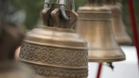 La mujer en blusa colorida suena en campanas de iglesia en tiempo del día metrajes