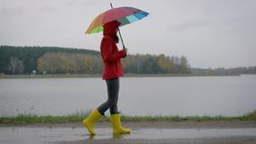 La mujer en botas amarillas y un paraguas pasa a través de los charcos en Autumn Day metrajes