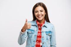 La mujer en camisa del control y chaqueta del dril de algodón muestra el pulgar para arriba Imagen de archivo