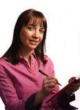 La mujer en camisa del fushia toma notas Foto de archivo libre de regalías