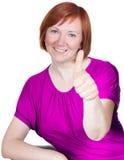 La mujer en camisa rosada es feliz y pulgar para arriba foto de archivo