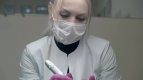La mujer en la capa blanca sobre el jersey negro sostiene el arma del tatuaje almacen de metraje de vídeo