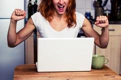 La mujer en casa es muy emocionada sobre su ordenador portátil Imagen de archivo libre de regalías