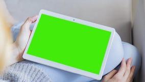 La mujer en casa relaja la lectura en la tableta Foto de archivo libre de regalías