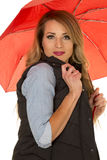 La mujer en chaleco negro y el control rojo del paraguas conceden sobre la barbilla Imagenes de archivo