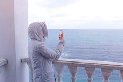 La mujer en la chaqueta blanca tira el vídeo de las ondas del mar en smartphone en terraza hermosa con la opinión del mar Visión  fotos de archivo