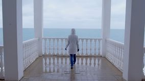 La mujer en la chaqueta blanca vino en terraza hermosa con la opinión del mar Visión posterior metrajes