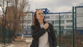 La mujer en chaqueta de cuero negra y una mochila negra camina abajo de la calle al lado del patio El sol brilla adentro metrajes