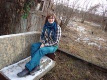 La mujer en chaqueta de la tela escocesa y bufanda de la cruz se sienta en el viejo exterior i del sofá Imagenes de archivo