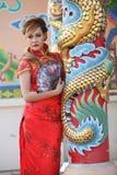 La mujer en chino viste el soporte al lado de un polo Fotos de archivo libres de regalías