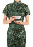 La mujer en chino viste sostener una taza de té fotografía de archivo libre de regalías