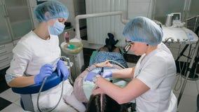 La mujer en la clínica del dentista consigue el tratamiento dental para llenar una cavidad en un diente Restauración dental y mat foto de archivo