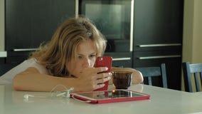 La mujer en la cocina utiliza la tableta, acaba de despertar Madrugada del desayuno metrajes