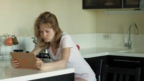 La mujer en la cocina utiliza la tableta, acaba de despertar Madrugada del desayuno almacen de video