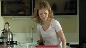 La mujer en la cocina utiliza la tableta, acaba de despertar Madrugada del desayuno almacen de metraje de vídeo