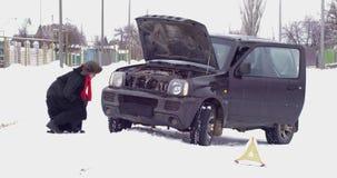 La mujer en el abrigo de pieles y el casquillo hechos de la piel de imitación da une vuelta y examina el coche arruinado la mucha almacen de video