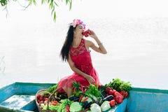 La mujer en el barco con las verduras come la pimienta Fotografía de archivo